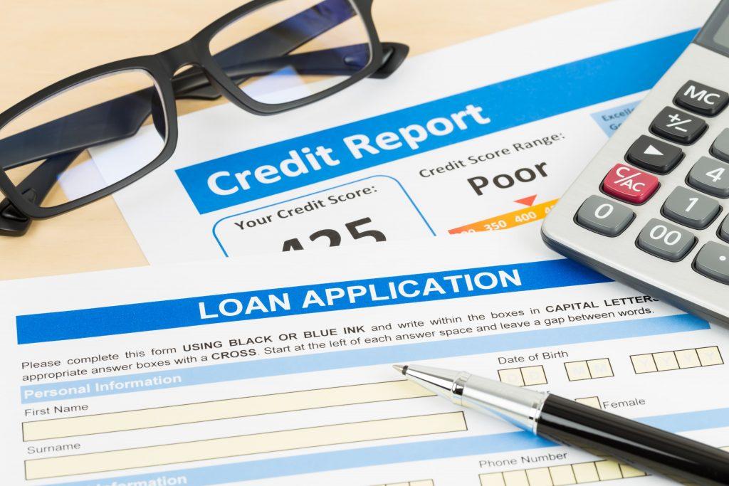 Credit Report, loan application, pen, and glasses