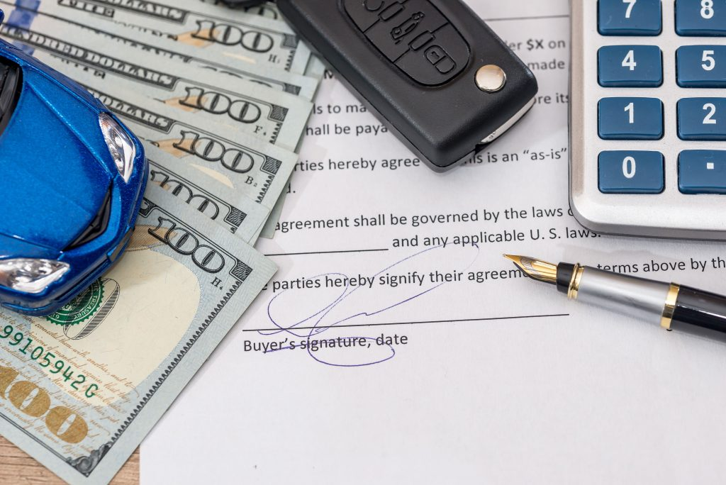 Blue car on top of cash, car keys, calculator, pen, and signed loan agreement